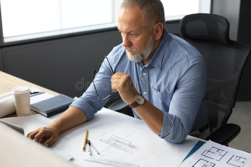 Senior businessman with a stylish short beard working on laptop computer at his office desk stock images