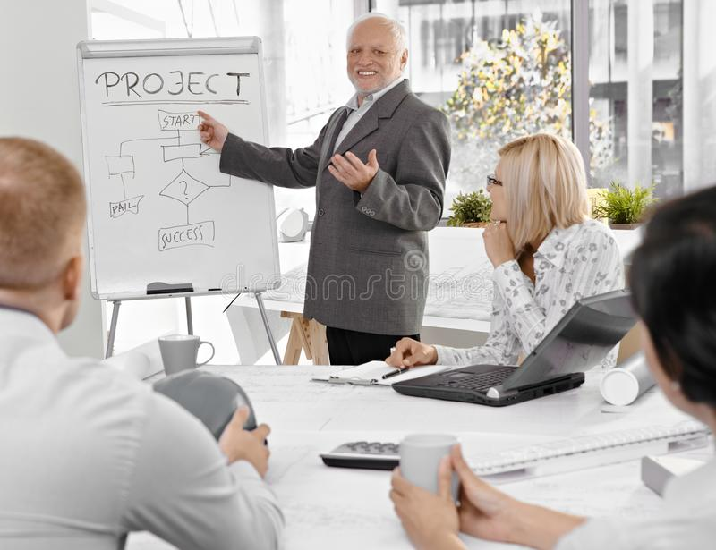 Senior businessman talking to colleagues stock photo