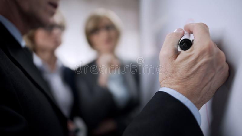 Senior businessman talking to younger colleagues and writing on board, planning stock photography