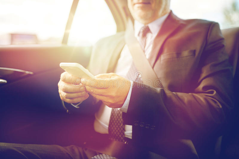 Senior businessman texting on smartphone in car royalty free stock photos