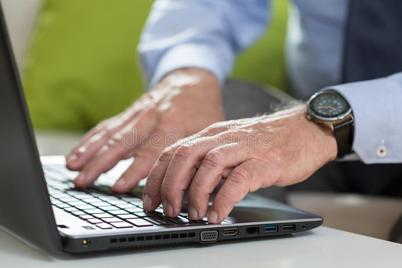 Senior businessman uses laptop for work royalty free stock photos