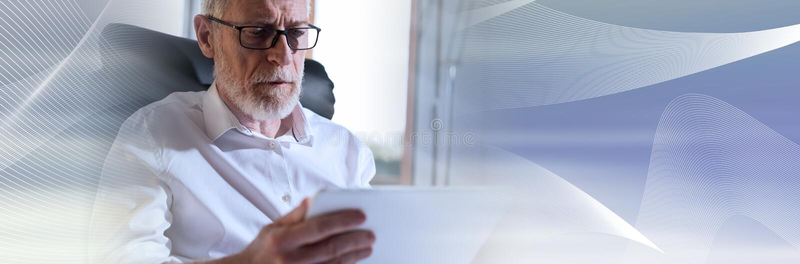 Senior businessman using a digital tablet. panoramic banner. Senior businessman using a digital tablet in office, hard light. panoramic banner stock photography