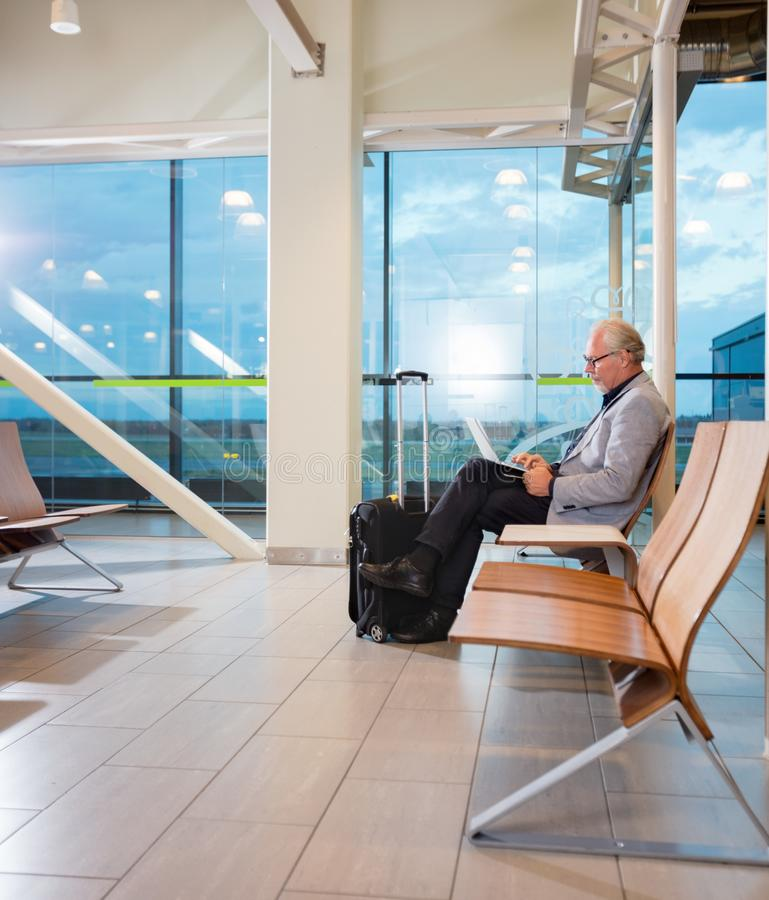 Senior Businessman Using Laptop At Airport Terminal stock photo