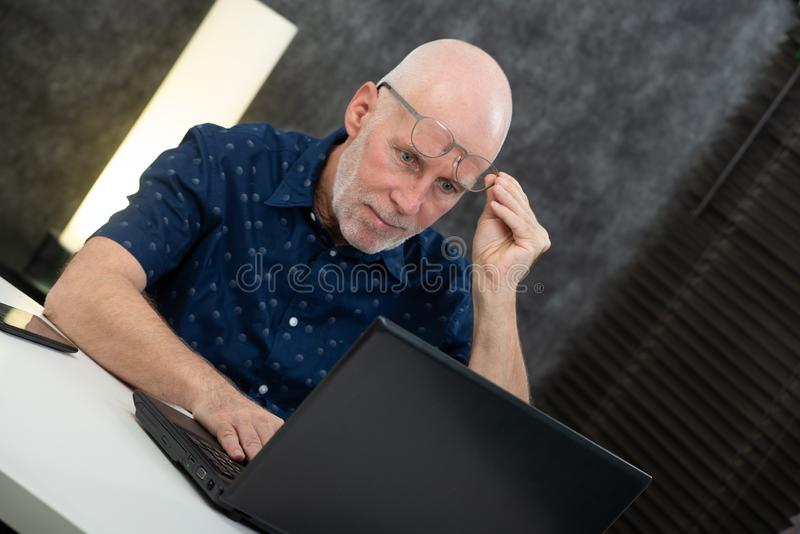 Senior businessman using laptop, he is having difficulties and vision problems. A senior businessman using laptop, he is having difficulties and vision problems stock photo