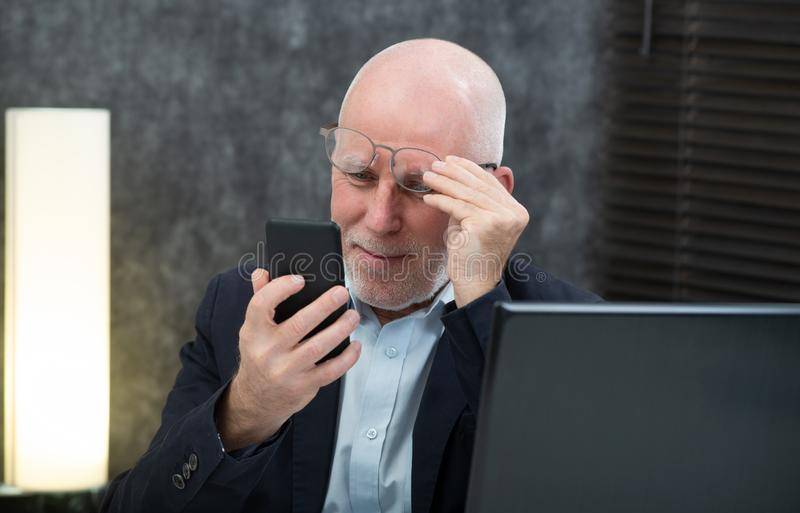 Senior businessman using smartphone, he is having difficulties and vision problems. A senior businessman using smartphone, he is having difficulties and vision stock images