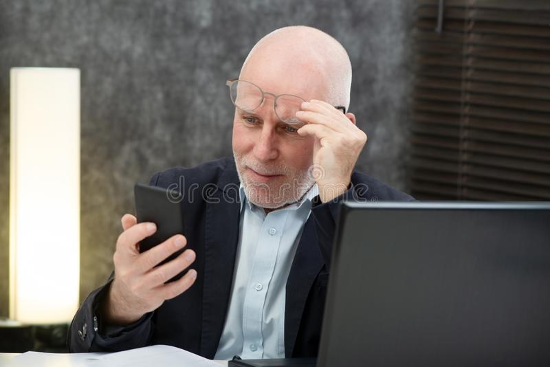 Senior businessman using smartphone, he is having difficulties and vision problems. A senior businessman using smartphone, he is having difficulties and vision stock image