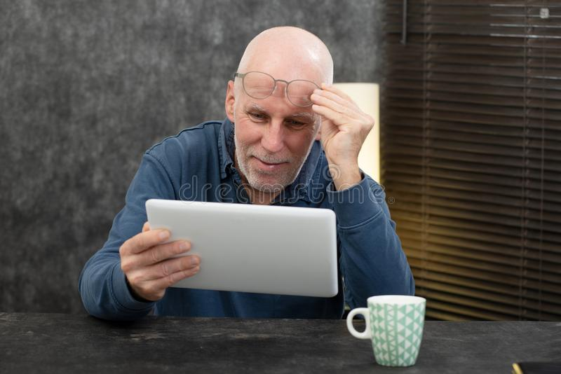 Senior businessman using tablet, he is having difficulties and vision problems. A senior businessman using tablet, he is having difficulties and vision problems stock photography