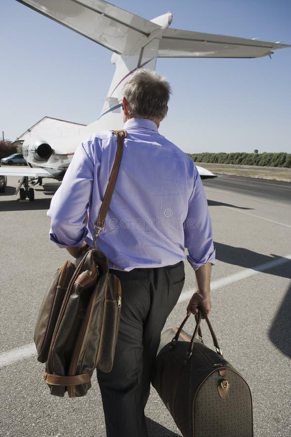 Senior Businessman Walking Towards Airplane royalty free stock photo