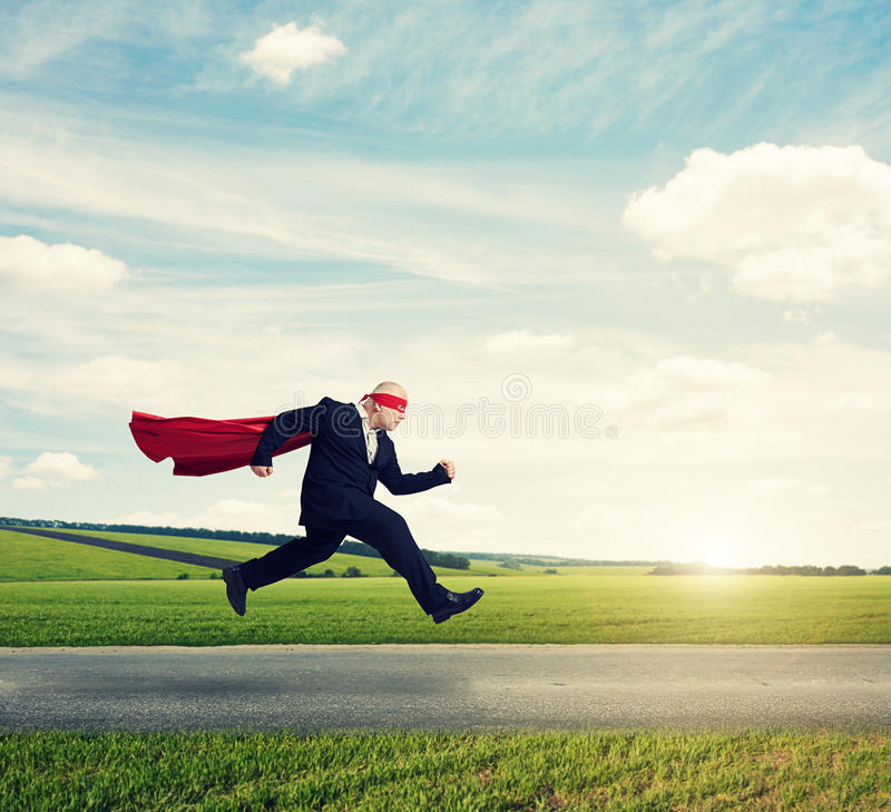 Senior businessman wearing like superhero. Very fast running on the road over green fields and blue sky stock image