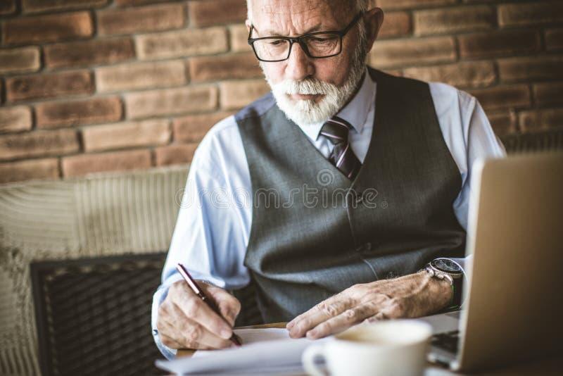 Senior businessman working in cafeteria. Senior businessman working on paper in cafeteria stock image