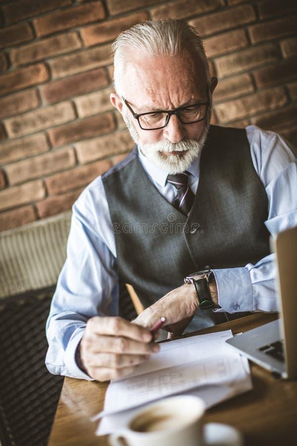 Senior businessman working in cafeteria. Senior businessman working on document in cafeteria stock photo