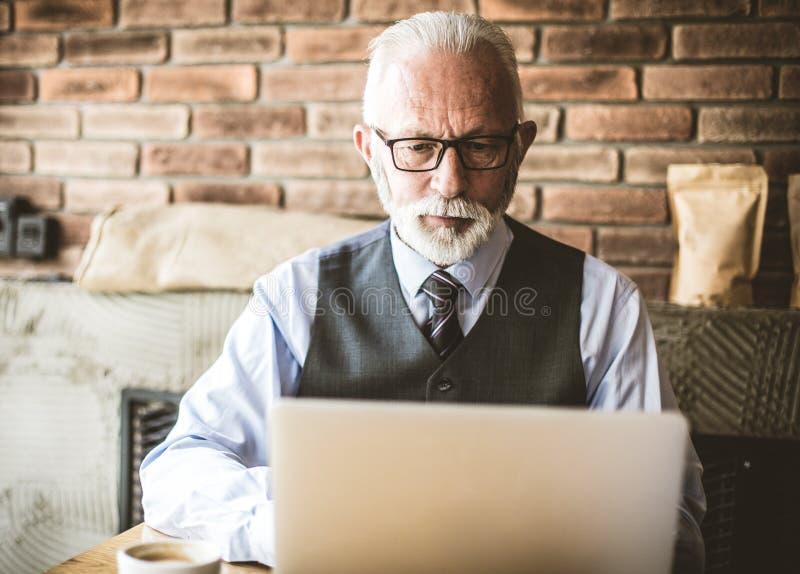 Senior businessman working in cafeteria. Senior businessman working on laptop in cafeteria stock images