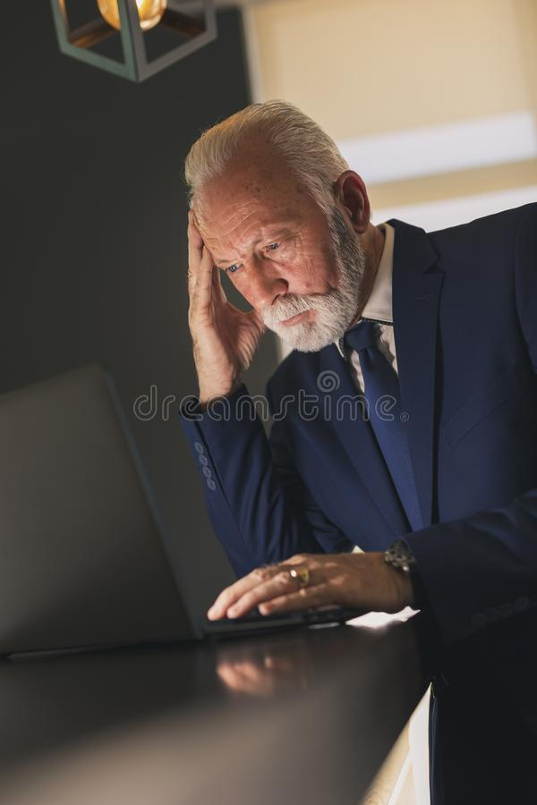 Senior businessman working on a laptop computer stock photography