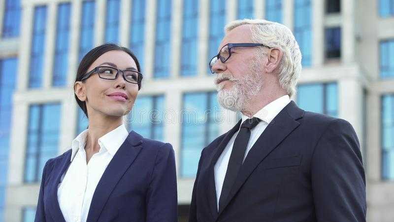 Senior businessman and young woman in suit looking each other, company teamwork royalty free stock image