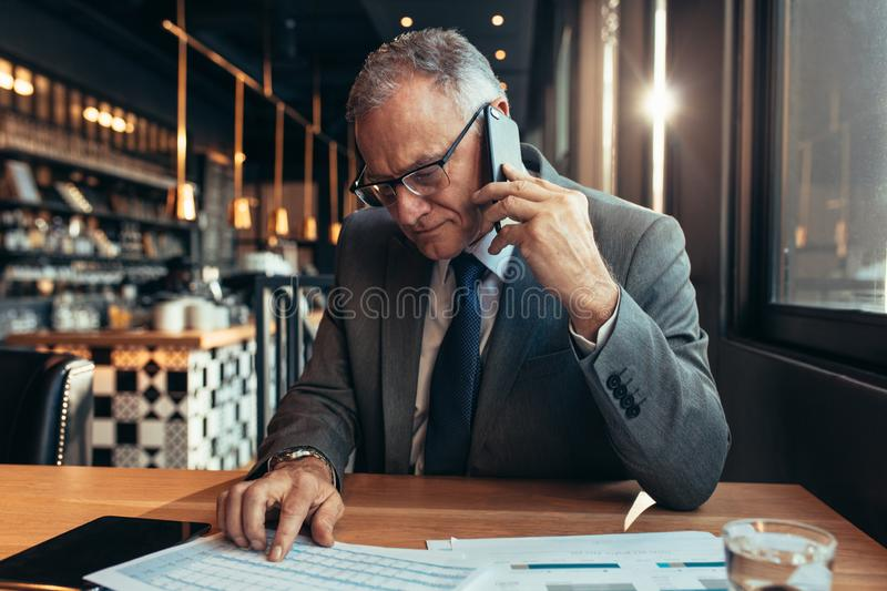 Senior businessmen discussing business figures over phone stock image