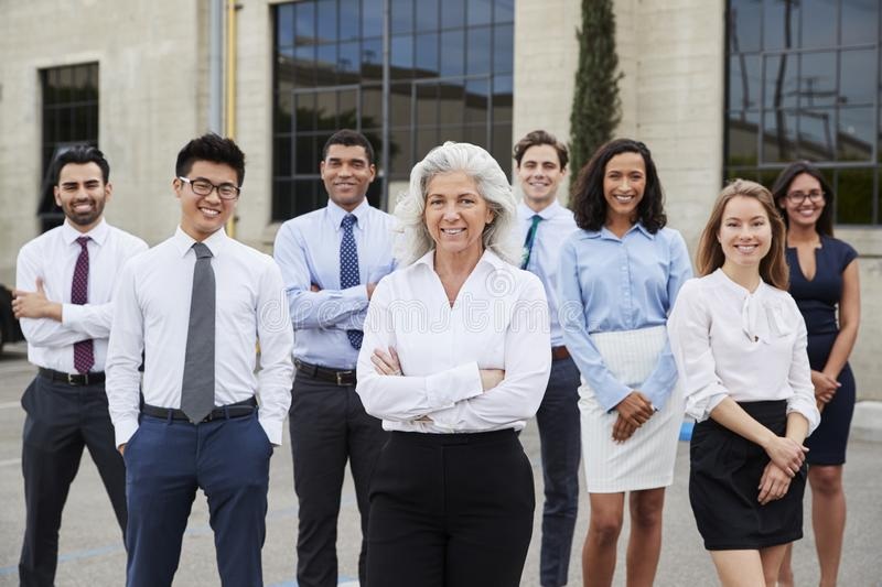 Senior businesswoman and colleagues outdoors, portrait stock images