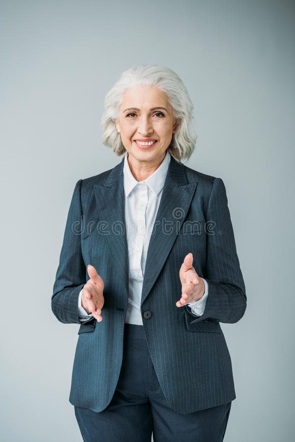 Senior businesswoman with extended hands isolated on grey stock photos