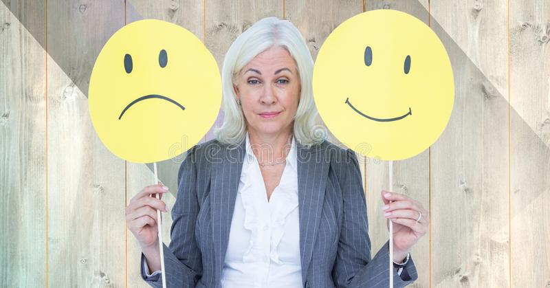 Senior businesswoman holding smiley faces against wooden background royalty free stock photo
