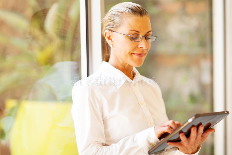 Senior businesswoman tablet computer. Senior businesswoman using tablet computer in office royalty free stock images
