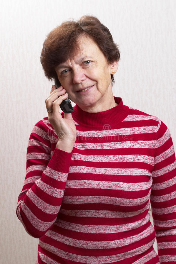 Senior on call. Senior woman on call in over light defocused wallpaper background stock photography