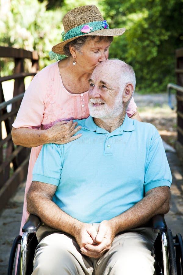 Senior Caretaker. Senior woman caring for her disabled husband