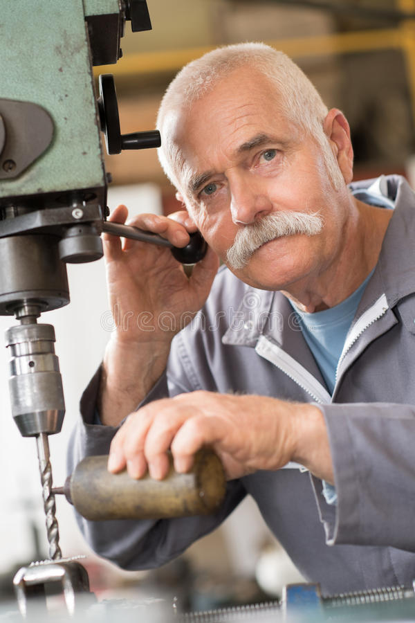 Senior carpenter drilling hole in metal plank in workshop royalty free stock photo