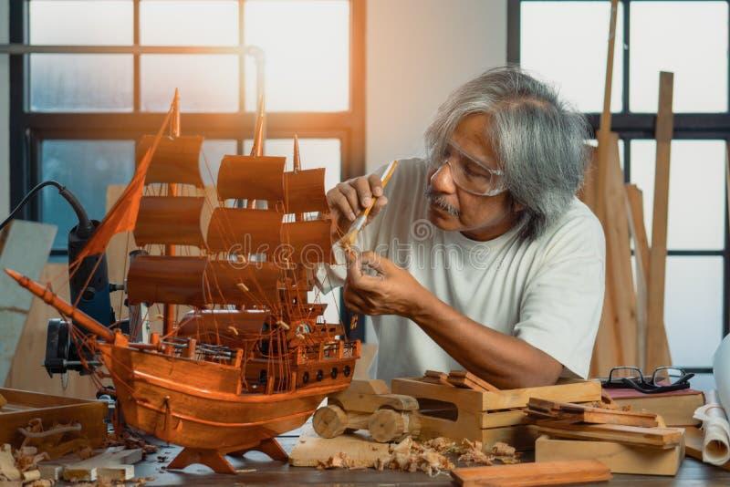 Senior carpenter furnishing wooden ship in home workshop royalty free stock photos