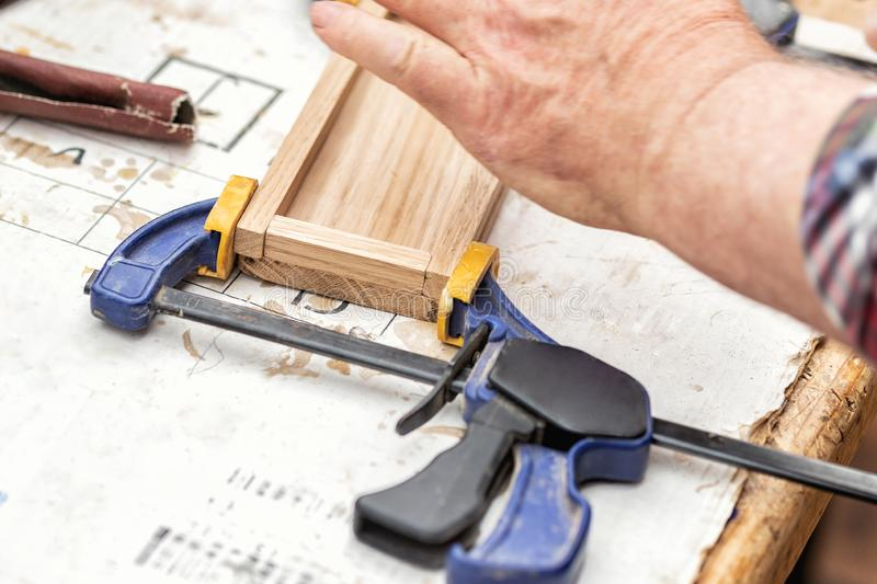 Senior carpenter glueing wooden craft surface and joining with clamps. Woodwork carpenter with equipment and tools at workshop. royalty free stock photos