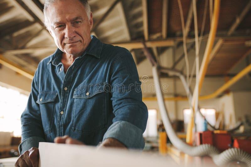 Senior carpenter inspecting the wooden bar royalty free stock photography