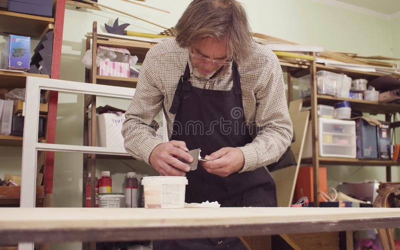 The senior carpenter spackling a wooden board royalty free stock photography