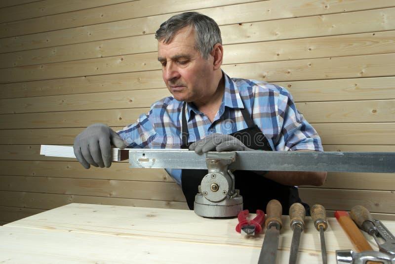Senior carpenter working in his workshop. Senior carpenter working in workshop stock image