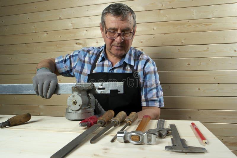 Senior carpenter working in his workshop. Senior carpenter working in workshop royalty free stock images