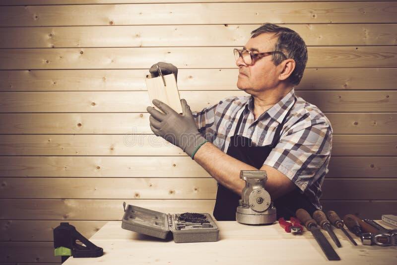 Senior carpenter working in his workshop. Senior carpenter working in workshop royalty free stock photography