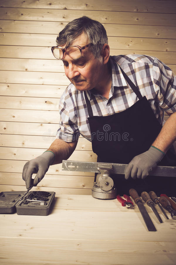Senior carpenter working in his workshop. Senior carpenter working in workshop royalty free stock photo
