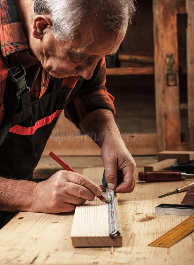 Senior carpenter working in his workshop. Senior carpenter marking a measurement on a wooden plank royalty free stock photos