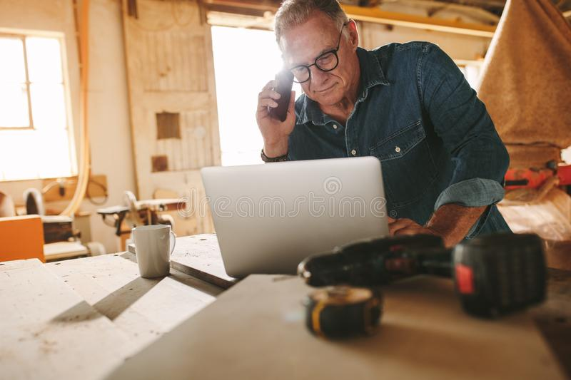 Senior carpenter working on laptop and phone in his workshop royalty free stock photo