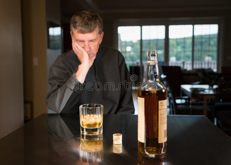 Senior caucasian adult man with depression. Senior adult male facing a kitchen table with alcoholic drink and looking very sad and depressed royalty free stock image