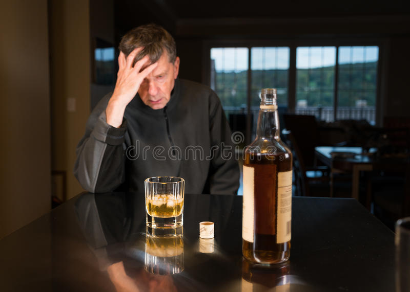 Senior caucasian adult man with depression. Senior adult male facing a kitchen table with alcoholic drink and looking very sad and depressed royalty free stock photo