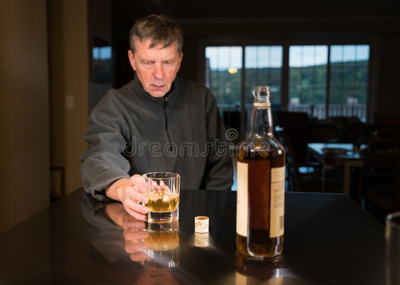 Senior caucasian adult man with depression. Senior adult male facing a kitchen table with alcoholic drink and looking very sad and depressed royalty free stock images