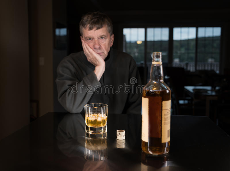 Senior caucasian adult man with depression. Senior adult male facing a kitchen table with alcoholic drink and looking very sad and depressed stock photography