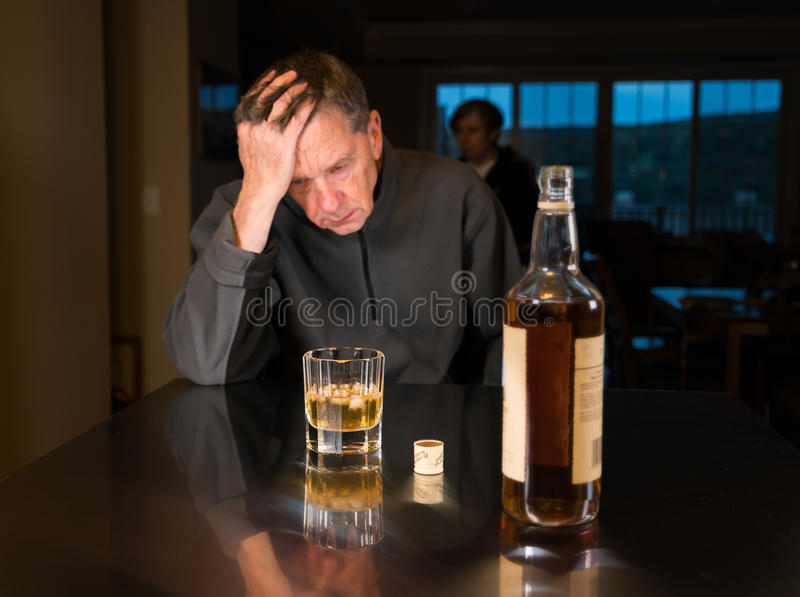 Senior caucasian adult man with depression. Senior adult male facing a kitchen table with alcoholic drink and looking very sad and depressed as wife is seen in stock photo