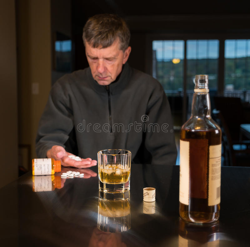 Senior caucasian adult man with depression. Senior adult male facing a kitchen table with alcoholic drink and looking very sad and depressed with tablets or royalty free stock photo