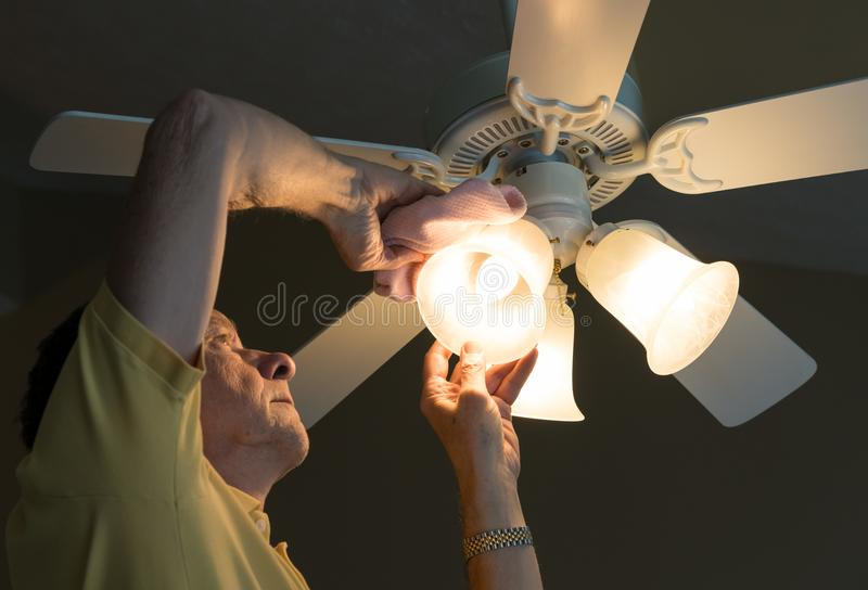 Senior caucasian man dusting lamp shade in ceiling fan and light. Senior adult male dusting the glass shade of a bulb in a ceiling fan and lighting fixture royalty free stock photography