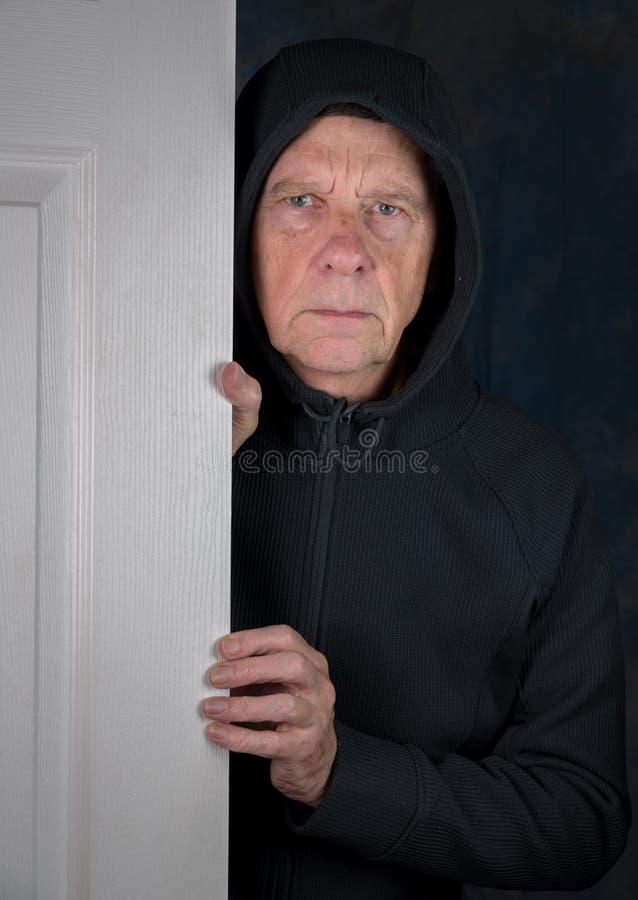 Senior caucasian man greeting visitor at doorway stock images