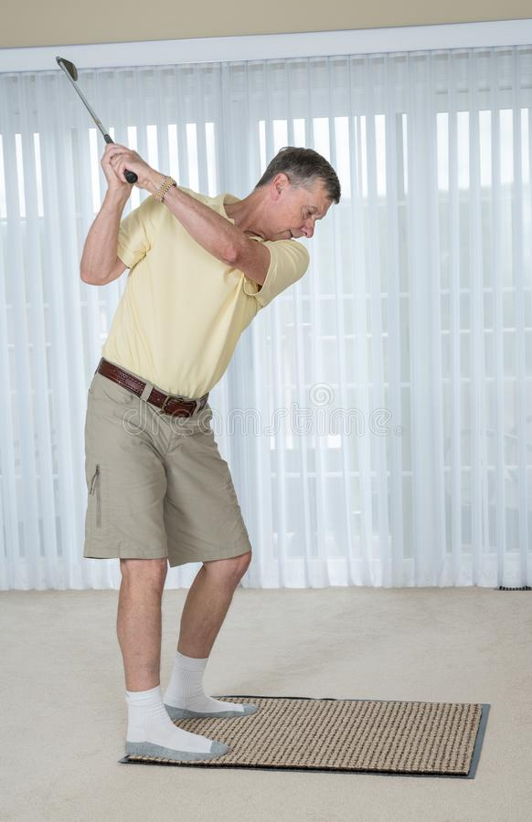 Senior adult man practicing golf grip and swing in bedroom royalty free stock photo