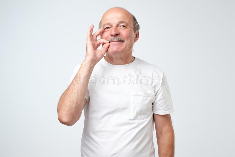 Senior caucasian man showing a sign of closing mouth and silence gesture doing like closing his mouth with a zipper stock images