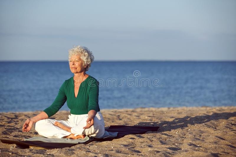 Senior caucasian woman meditating on the beach stock images