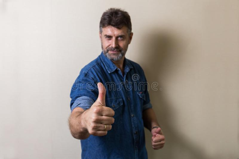 Senior Caucasians man make thumbs up. On abstract backgeound royalty free stock photo