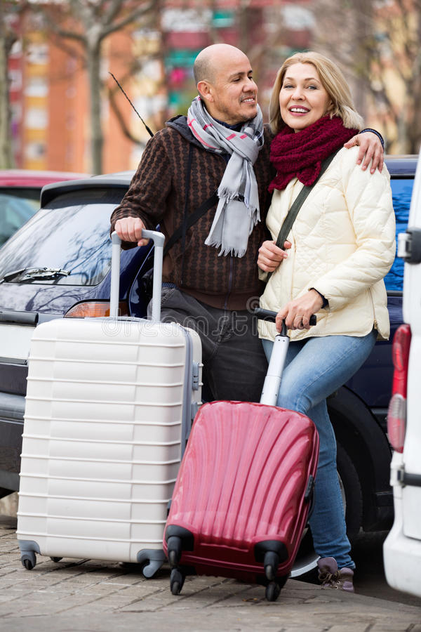 Senior charming couple of travellers posing with trollers stock image