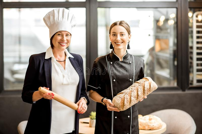 Senior chef confectioner with young assistant in the bakery shop royalty free stock photography